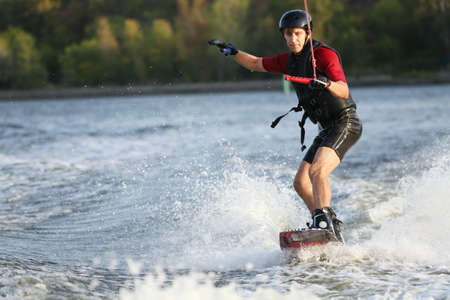 wakeboarding: Wakeboarder surfing across the river