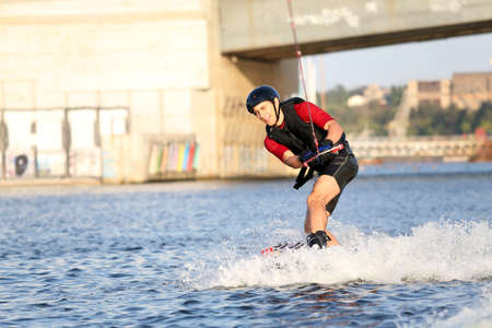 Wakeboarder surfing across the river photo