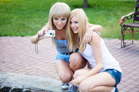 Two beautiful young girl friends with a digital photo camera photo