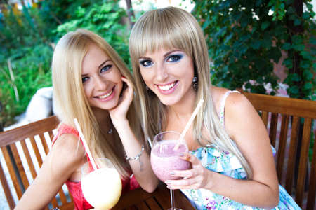 Pretty young women drinking smoothie in a cafe photo