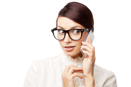 Strict woman in large glasses with a cell phone, isolated on white background photo