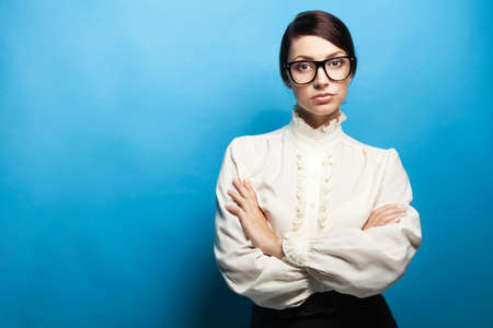 Strict woman in large glasses, blue background photo
