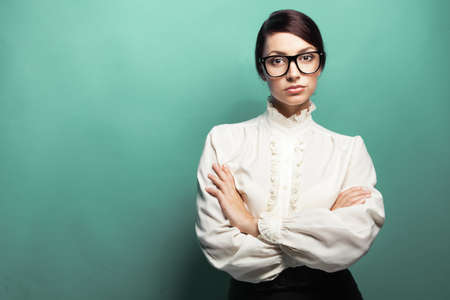 Strict woman in large glasses, green background Stock Photo - 15384833