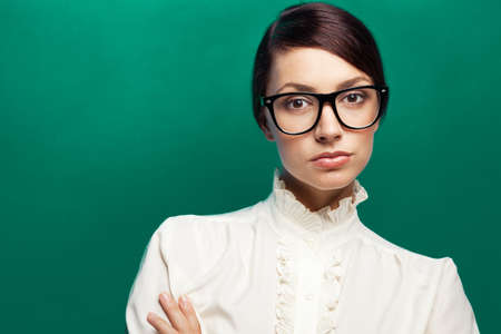 Strict woman in large glasses, green background Stock Photo - 15831991
