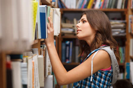 library book: Beautiful female student in a university library Stock Photo