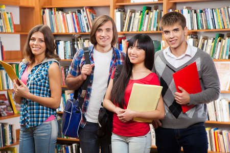 Group of happy students in a library Stock Photo - 16014526