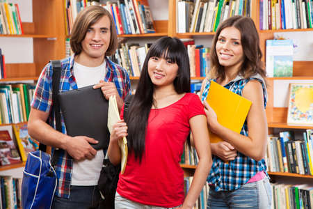 Group of happy students in a library Stock Photo - 16117945