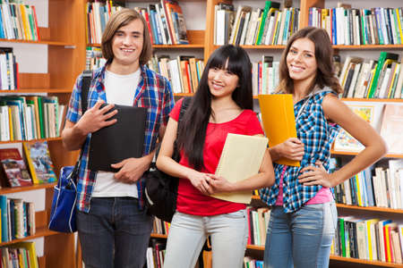 Group of happy students in a library photo