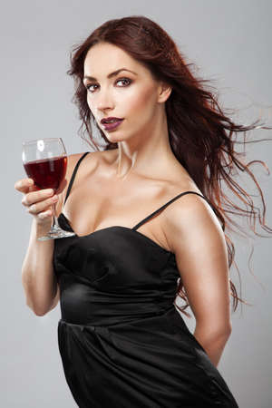 Gorgeous brunette in black dress with a glass of wine photo