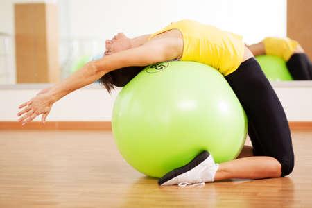 pilates: Femme faisant de remise en forme dans un gymnase sur un ballon Banque d'images