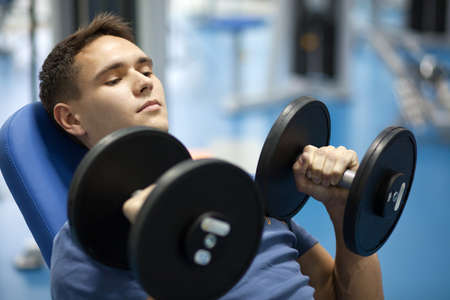 weight training: Handsome man with dumbbells in a gym