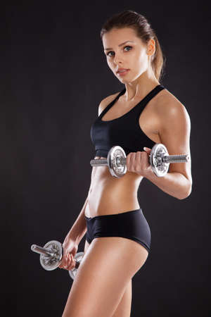 Sporty woman with dumbbells studio photo
