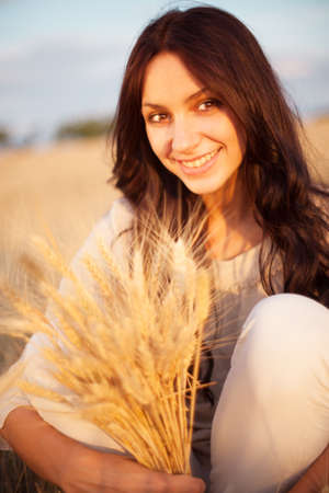 Beautiful brunette lady in wheat field at sunset Stock Photo - 17567650