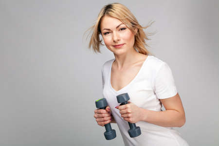 Young woman working out with dumbbells photo