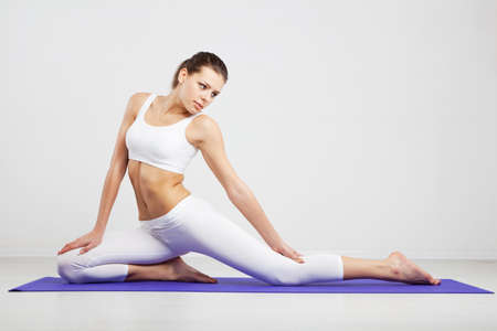 Woman doing stretching exercises in a gym photo