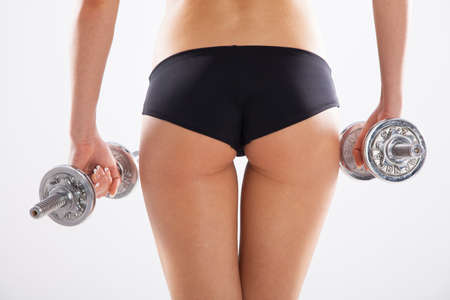 buttock: Mujer delgada con pesas, fondo blanco Foto de archivo