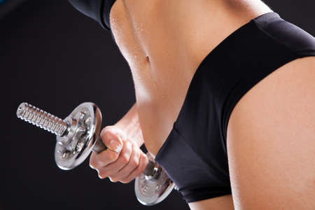 Slim woman with dumbbells, black background photo