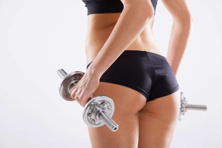 woman buttocks: Slim woman with dumbbells, white background Stock Photo