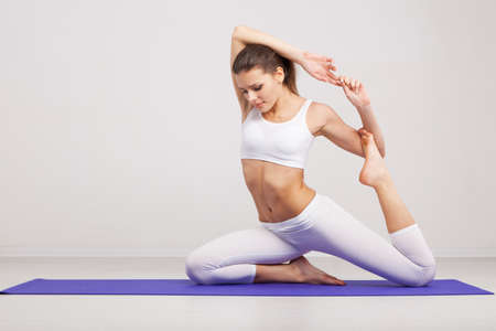 mats: Woman doing stretching exercises in a gym