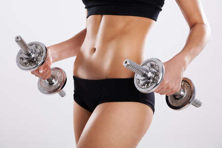 muscle belly: Slim woman with dumbbells, white background Stock Photo