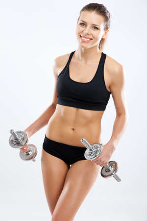 Slim woman with dumbbells, white background photo