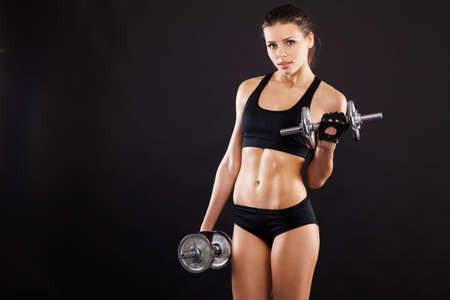 Slim woman with dumbbells, black background
