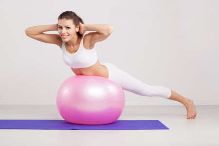 Woman on a fitness ball in a gym photo