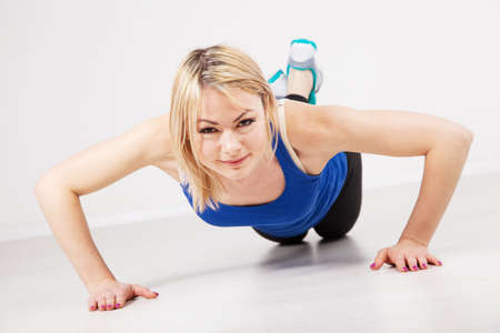 Sporty woman doing push ups in a gym photo