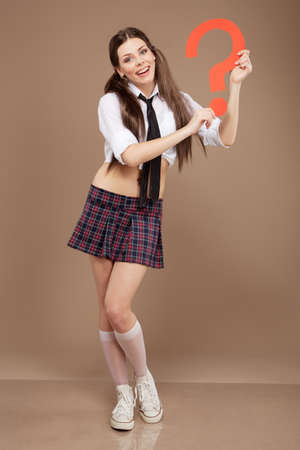 Woman in a schoolgirl costume holding a question mark photo