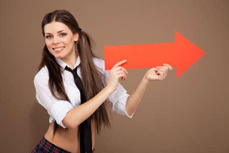 schulm�dchen: Frau in ein Schulm�dchen Kost�m h�lt einen Pfeil Zeichen