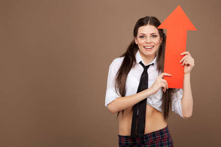 Woman in a schoolgirl costume holding an arrow sign photo