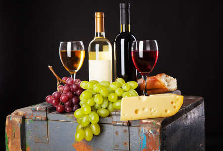 Wine, grapes and cheese on black background photo