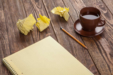 copywriting: Notepad on a wooden table with crumpled sheets around