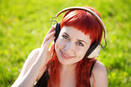 Pretty girl listening to music on green grass background photo