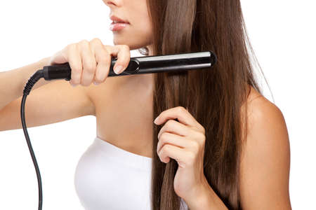 Young woman iwth a hair straightener, white background Stock Photo