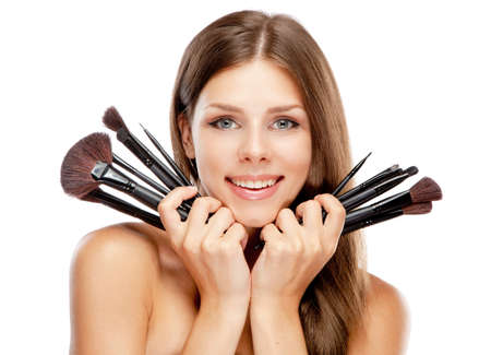Beautiful woman holding makeup brushes, isolated on white background photo