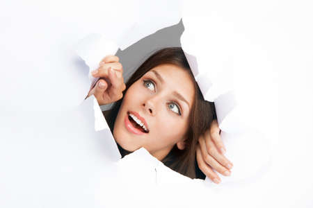 Young woman breakign through a paper sheet photo