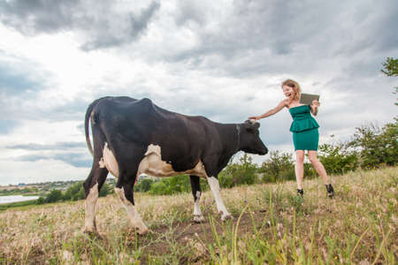 Young woman and a cow in the countyside photo
