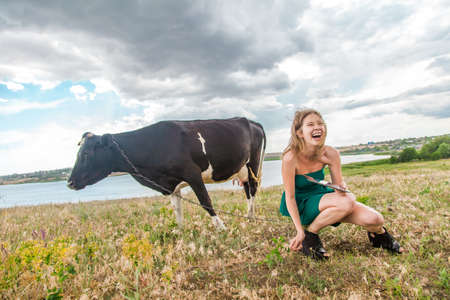 Young woman and a cow in the countyside Stock Photo - 22152448