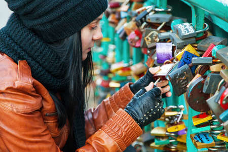 Girl opening a lock on a bridge Banque d'images