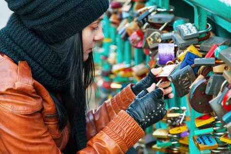 Girl opening a lock on a bridge Stock Photo
