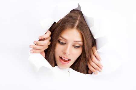 Young woman breaking through a paper sheet. photo