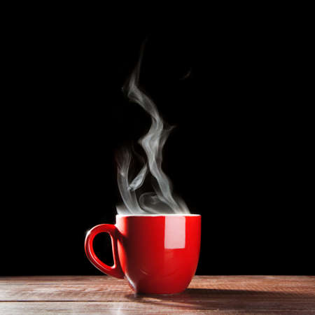 cup of coffee: Steaming coffee cup on dark