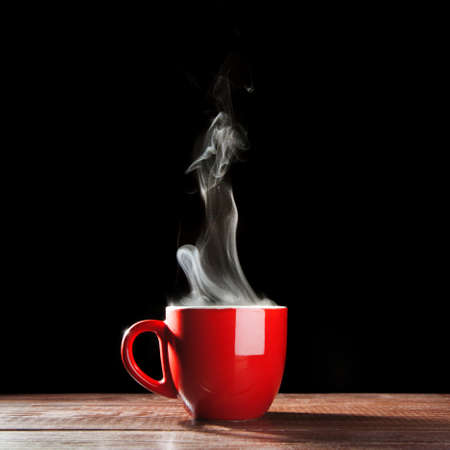 red cup: Steaming coffee cup on dark