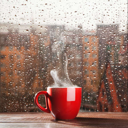morning coffee: Steaming coffee cup on a rainy day window  Stock Photo