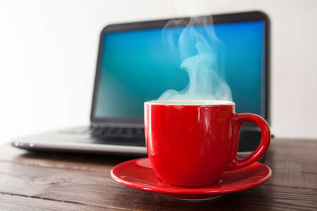 Laptop and a cup of coffee on a table Stock Photo