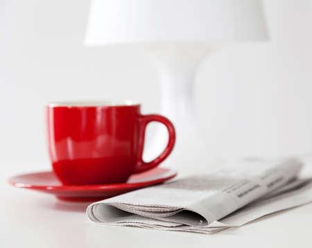 negocios comida: Peri�dico y una taza de caf� sobre una mesa blanca Foto de archivo