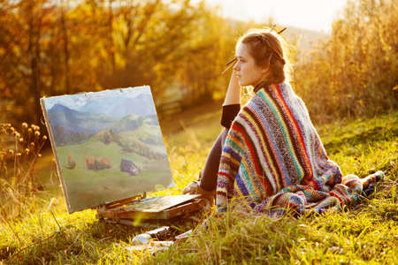 Young artist painting an autumn landscape Banque d'images