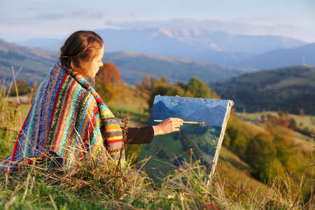 Young artist painting an autumn landscape photo