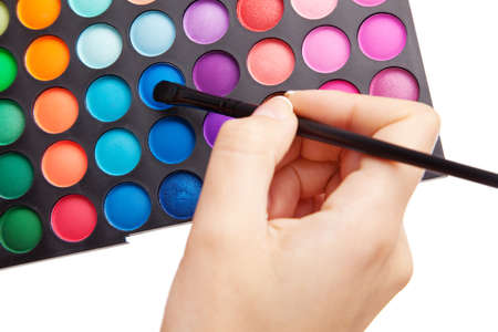 Female hand holding a makeup palette, white background photo